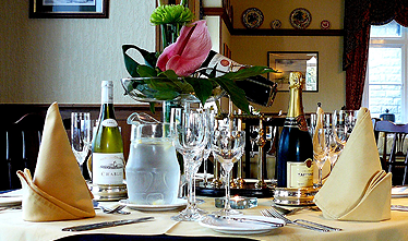 an image showing one of their dining tables laid out with plates and cutlery, serviettes, jug of watter and champagne