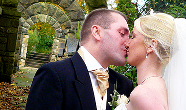 a close up image of the bride and groom kissing in the grounds outside after just getting married